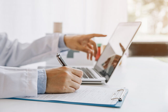 Doctor in hospital writing medical documentation and using laptop