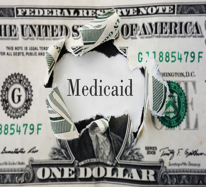 Torn dollar with medicaid written in the center