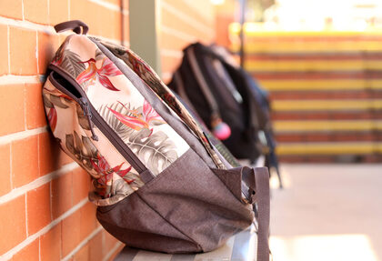 close up of school bags backpacks on a steel bench chair outside a classroom with steps stairs in the background. Education teacher student concept.