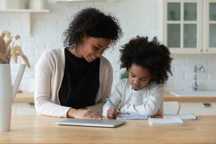 African American young mother and little daughter sit at desk in kitchen studying online together, biracial mom and small girl child handwrite, do homework, learning at home, homeschooling concept