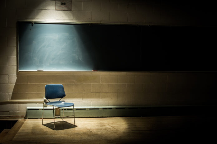 Empty schoolroom in Kentucky with a spotlight on a lone chair