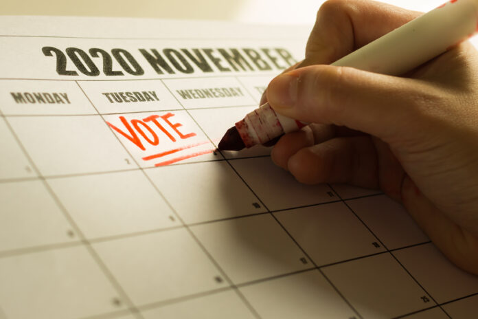 A american voter writing a reminder note on the calender to vote.