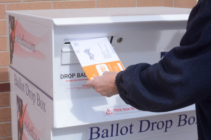 Hand putting Jefferson County Colorado election ballot envelope into ballot drop box in early voting mail election