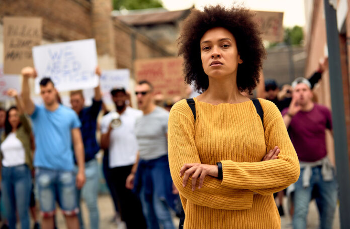 Young black woman with arms crossed standing in front of crowd of people on anti-racism protest.