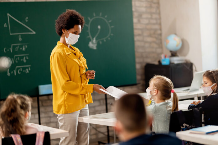 Happy black teacher and her students wearing protective face mask in the classroom. Teacher is giving them their test results.