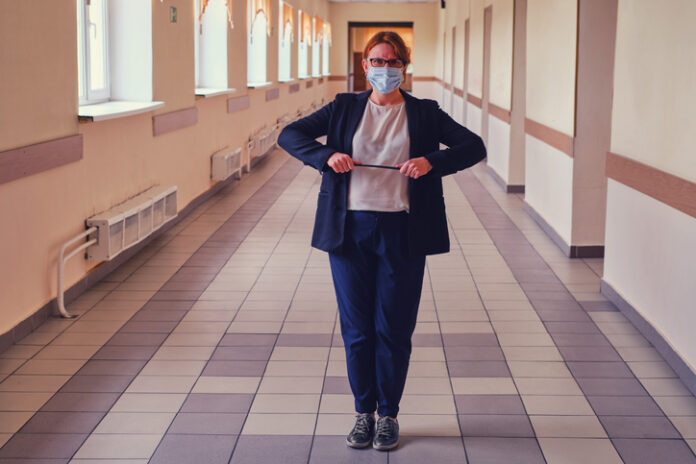 An angry teacher in a medical mask is standing in an empty school corridor. Female teacher during coronavirus quarantine