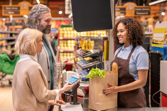 Mature female with smartphone paying for food products in supermarket while standing by her husband in front of happy young cashier