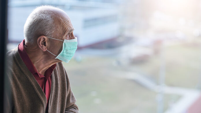 medical care, aged pensioner man with gray hair wearing medical facemask looking through window health care concept