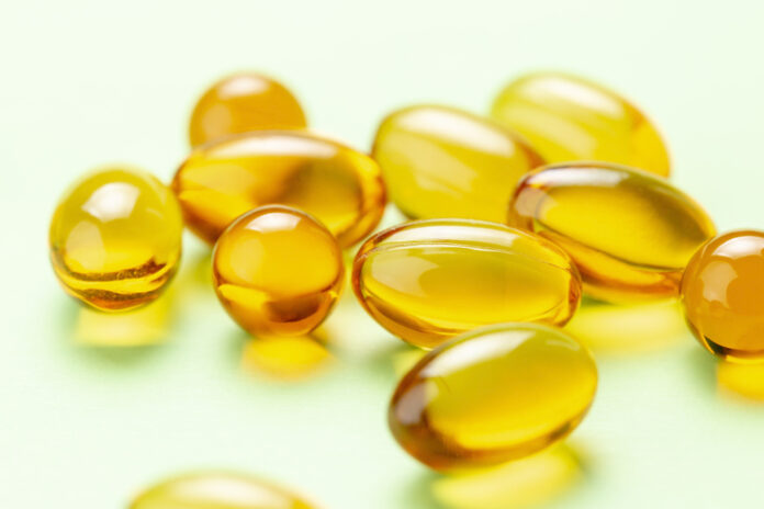 Close up of Vitamin D Omega 3 fish oil capsules on green background