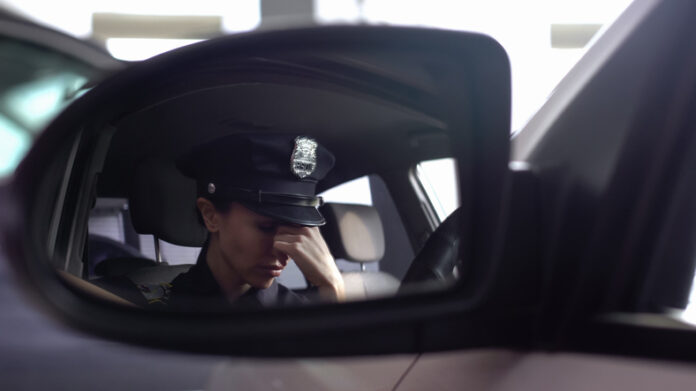 Tired police woman feeling headache, sitting in patrol car, stressed lifestyle