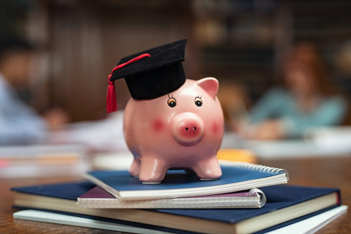 Piggy bank wearing mortar board on pile of books in library while students studying in background. Saving money for college with piggy bank on books in library. Savings and education debt concept.