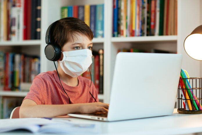 Young student wearing surgical mask doing his homework on computer.