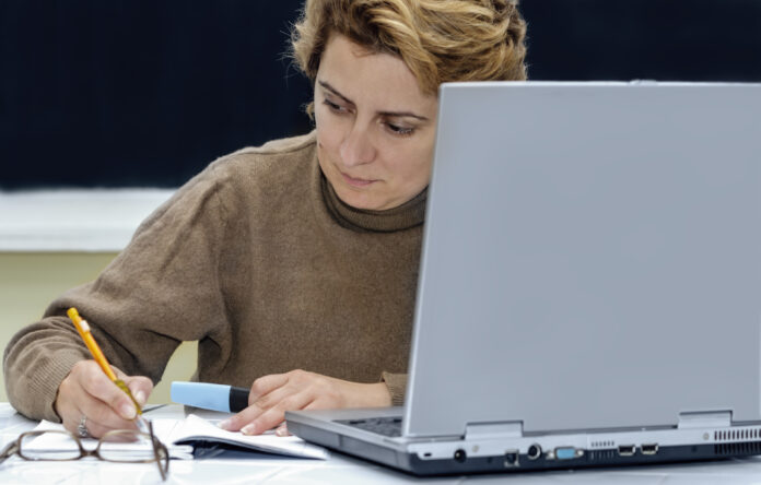 Female scientist working in front of her laptop in a laboratory.