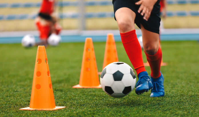 Footballer dribbling ball on training between orange cones. Young football player in sports blue cleats and red socks