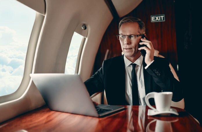 Rich businessman in suit is working on a laptop and speaking on mobile phone while flying in private jet.