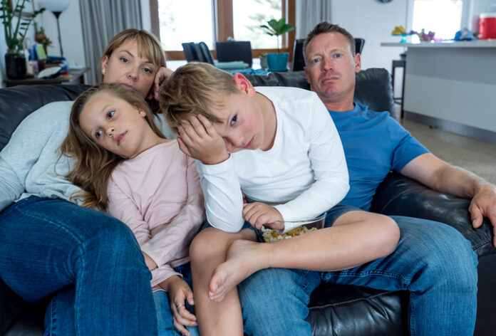 Coronavirus lockdow. Bored family watching tv helpless in isolation at home during quarantine COVID 19 Outbreak. Mandatory lockdowns and self isolation recommendations forces families stay home.