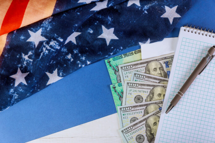 US dollar cash banknote on American flag COVID-19 on global pandemic lockdown, financial stimulus package government for people