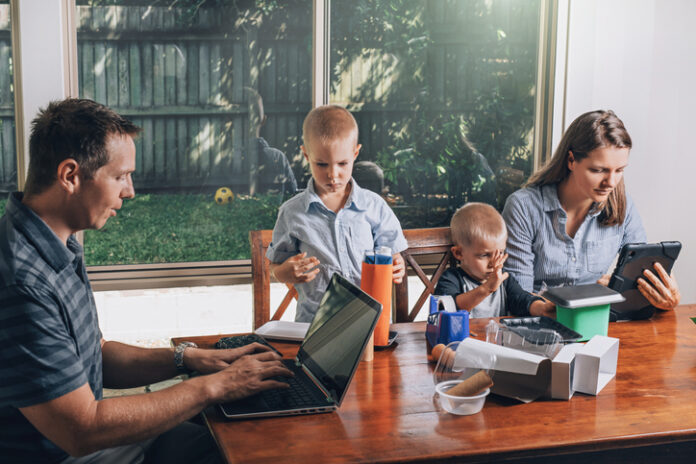 Concept of work from home and home schooling. Woman and man work on the Internet in a laptop and tablet while kids making crafts from recycled materials.