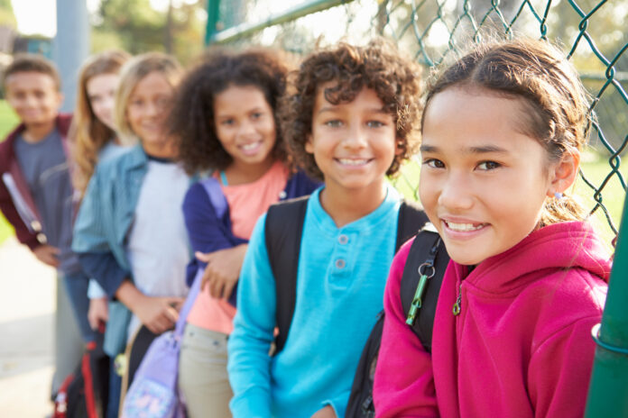 School choice, Group Of Young Children Hanging Out In Playground Smiling To Camera