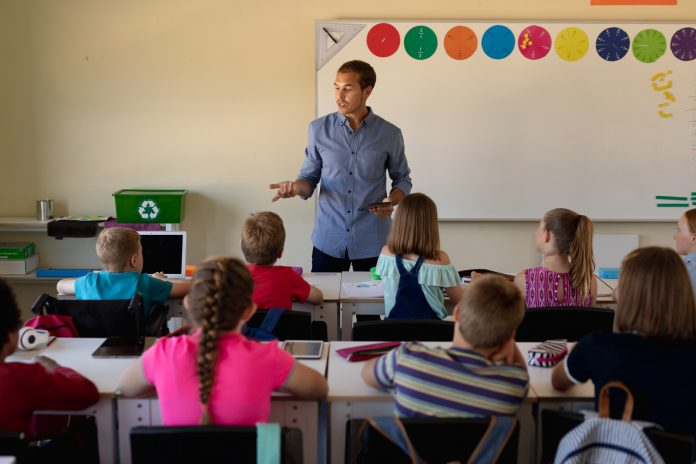 Front view of a Caucasian male school teacher standing and addressing a diverse group of school children sitting at desks during a lesson in an elementary school classroom in California