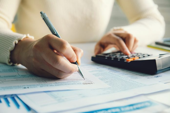 Woman filling form of Individual Income Tax Return,