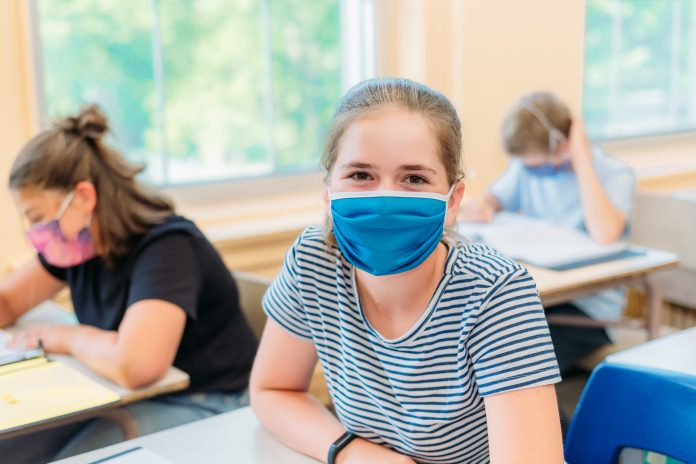 A thirteen year old girl is sitting at her desk in class with others students around her. She is wearing a mask to protect herself from Covid-19. She is looking at the camera. The others students around her are working.