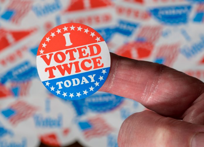 Finger with I Voted Twice button in front of many stickers given to US voters in Presidential election to illustrate vote fraud