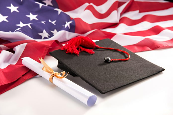Close-up view of graduation mortarboard, diploma and us flag on white, education concept, Washington