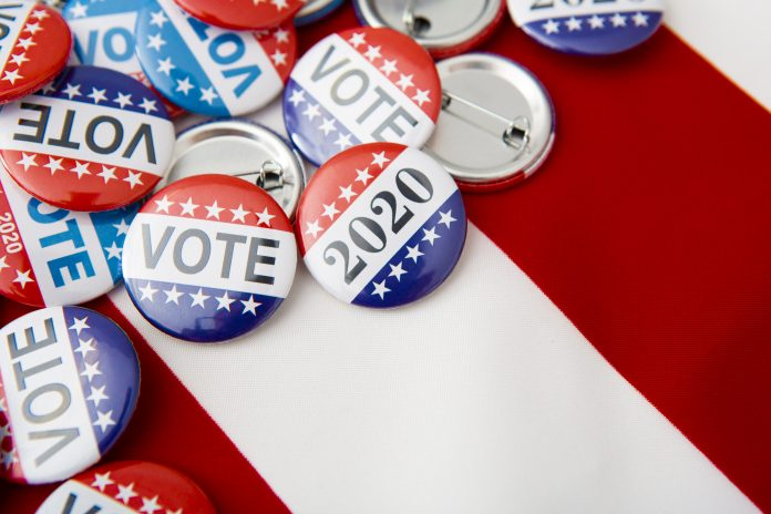American vote badges on national USA flag background, copy space, elections 2020