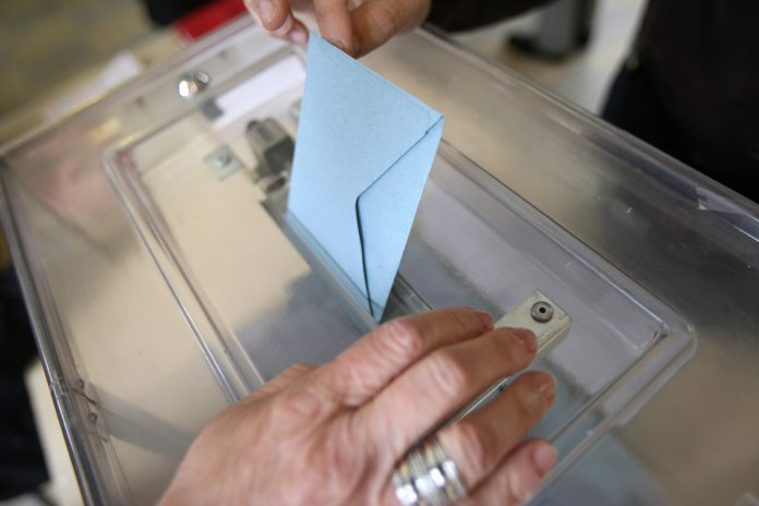 France. 05/06/2012. This colorful image depicts a man placing an election envelope in a plastic ballot box at a polling station.
