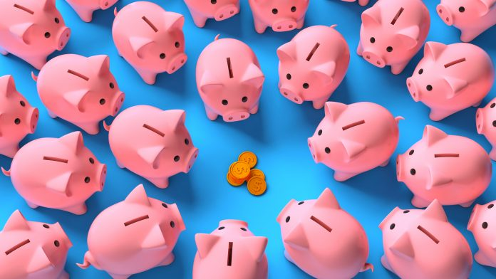 Lots of pink piggy banks around a stack of money coins on a blue background. Profit sharing. Saving income. Top view. 3d render.