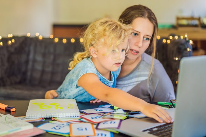 A teacher, a tutor for home schooling and a teacher at the table. Or mom and daughter. Homeschooling.
