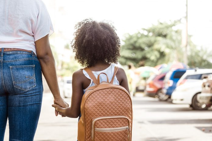 little girl with backpack holds a person's hand. back to school concept.