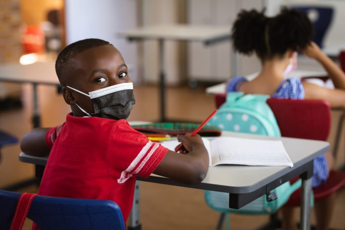 Portrait of african american boy wearing face mask sitting on his desk in class at elementary school. back to school and education concept