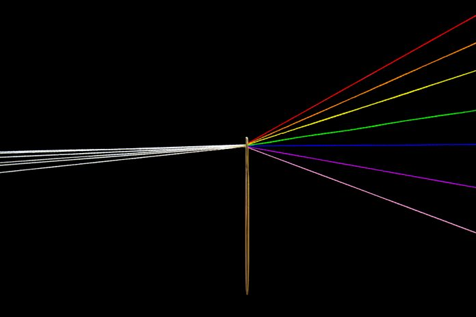 Photo includes Pink Floyd prism made of threads and needle. In the left side the thread is white and in right side the threads are the colors of the rainbow.