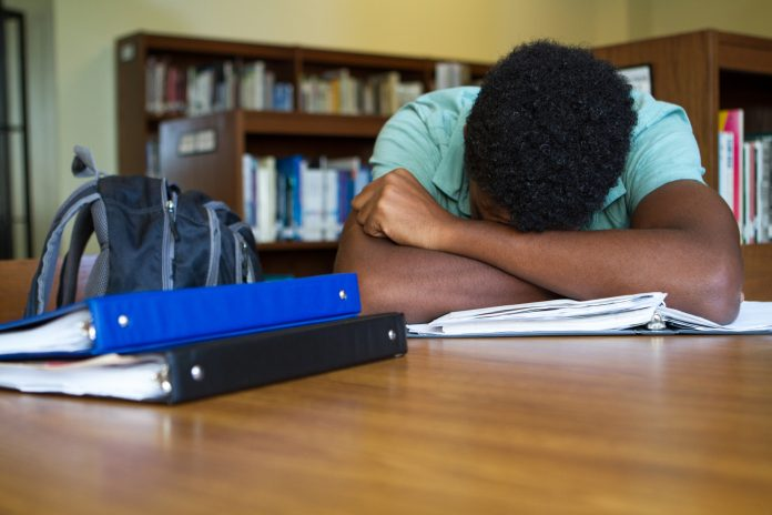 African American student overwhelmed with homework, learning loss