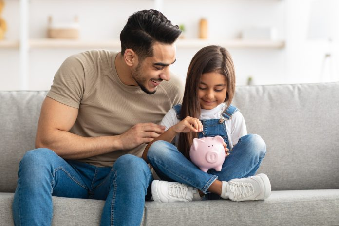 Financial Education For Children Concept. Portrait of cute smiling little girl putting coin in pink piggy bank, sitting with dad on the couch at home, man teaching his daughter how to invest